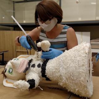 Image of Elena Baca, visual arts educator, fixing a piñata with a hot glue gun.