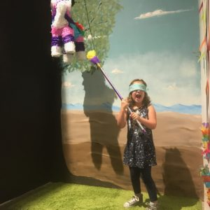 a young girl wearing a mask over her eyes, preparing to hit a piñata