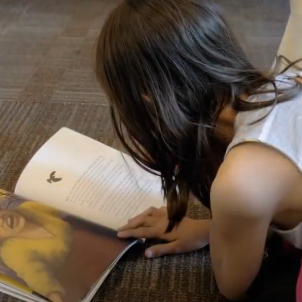 a girl reading a book on the floor